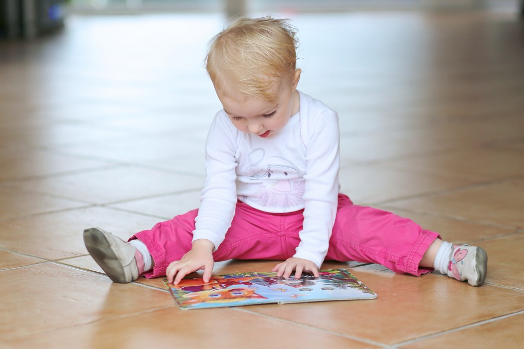 smart toddler girl reading book sitting indoors on tiles floor